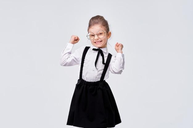 Portret van leuk charmant schattig meisje in schooluniform Premium Foto