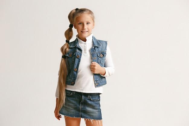 Portret van leuk klein tienermeisje in modieuze jeanskleren die camera bekijken en tegen witte studiomuur glimlachen. kindermode concept Gratis Foto