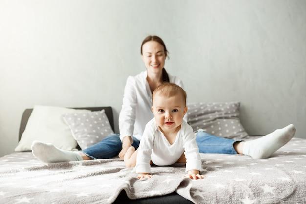 Portret van lieve kleine baby zittend met moeder op bed en kruipen in camerarichting met geïnteresseerde en opgewonden uitdrukking. Gratis Foto