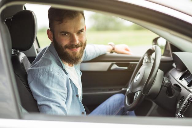 Portret van man zit in de auto Gratis Foto