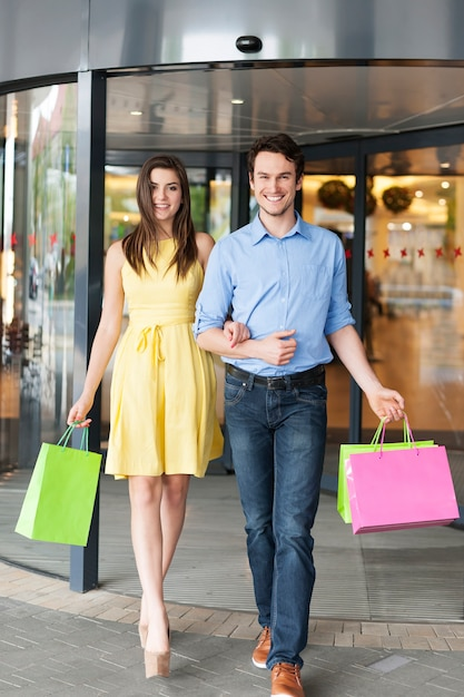 Portret van manierpaar na succesvol winkelen Gratis Foto