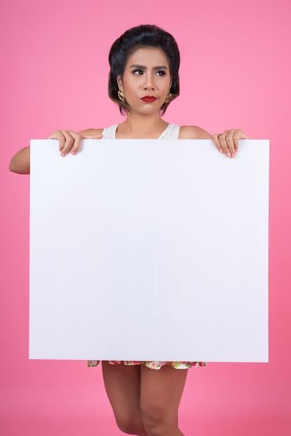 Portret van maniervrouw die witte banner toont Gratis Foto