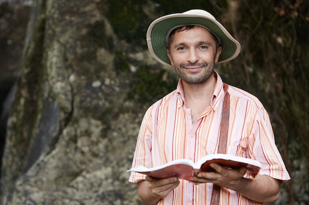 Portret van mannelijke botanicus of bioloog met stoppels die panamahoed en gestreept overhemd dragen bij veldwerk, notitieboekje in zijn handen houden met gelukkige en vrolijke uitdrukking Gratis Foto