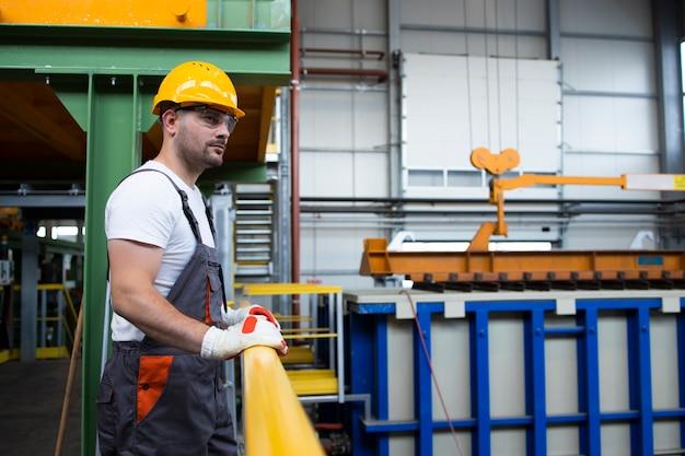 Portret van mannelijke fabrieksarbeider leunend op metalen balustrades in industriële productiehal Gratis Foto