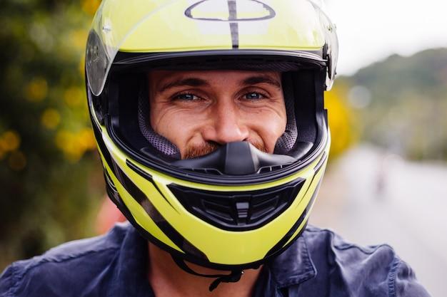 Portret van mannelijke fietser in gele helm op motor aan kant van drukke weg in thailand Gratis Foto