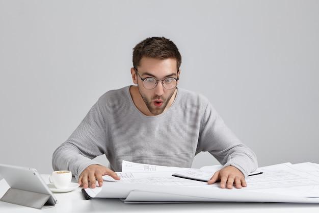 Portret van mannelijke ingenieur staart naar tekeningen, kijkt verbaasd, probeert te begrijpen wat er staat Gratis Foto
