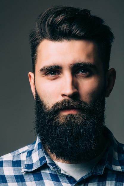 Portret van mannelijkheid. portret van knappe jonge bebaarde man terwijl hij tegen een grijze muur staat Gratis Foto