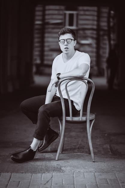Portret van mannen zittend op een stoel met wit t-shirt en zonnebril in de straat Gratis Foto