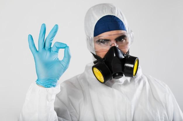 Portret van mannetje met gezichtsmasker dat ok teken toont Gratis Foto