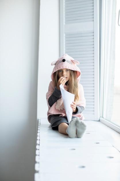 Portret van meisje dat roze trui draagt Gratis Foto