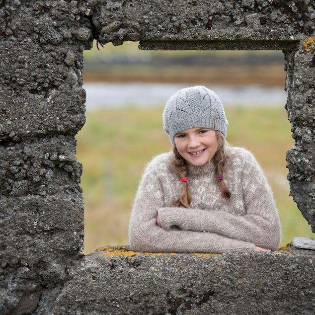 Portret van meisje door het raamkozijn van de rotsmuur Premium Foto