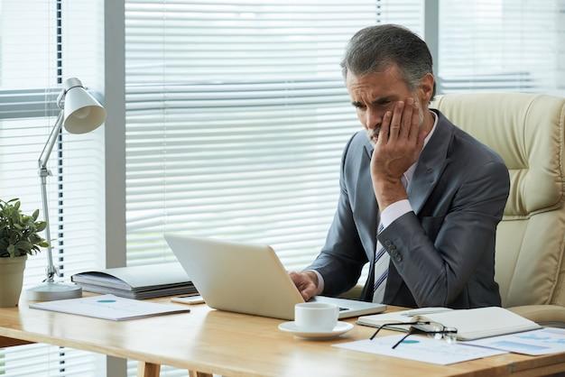 Portret van middelbare leeftijd ondernemer te weten komen over faillissement met gefrustreerd gebaar Gratis Foto