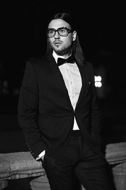 Portret van mode elegante langharige jonge man. aantrekkelijk en knap mannelijk model in zwart pak met snor in de straat 's nachts Gratis Foto