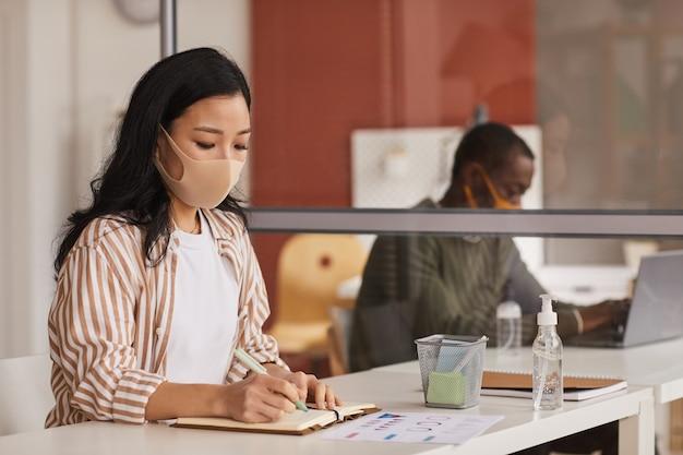 Portret van moderne aziatische onderneemster die masker draagt en in planner schrijft terwijl het werken in bureaucel, exemplaarruimte Premium Foto