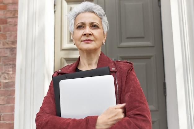Portret van modieuze 50-jarige blanke vrouw met draagbare computer poseren buiten haar huis Gratis Foto