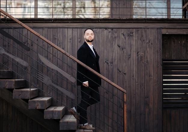 Portret van modieuze goed geklede man met baard poseren buitenshuis Gratis Foto