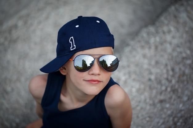 Portret van modieuze kleine jongen in zonnebril en cap. childhood. summertime. Premium Foto