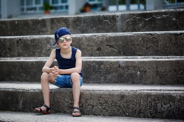 Portret van modieuze kleine jongen in zonnebril en pet aanbrengen op stenen trappen. childhood. summertime. Premium Foto