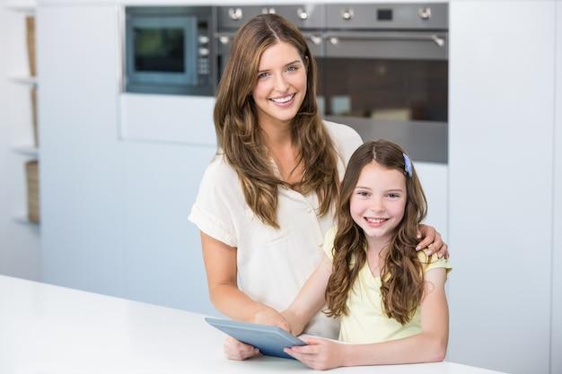 Portret van moeder en dochter met digitale tablet Premium Foto