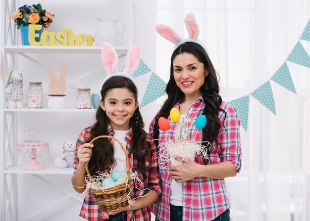 Portret van moeder en haar dochter die kleurrijke paaseieren in hand houden Gratis Foto