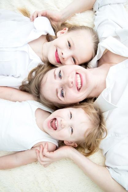 Portret van moeder en haar dochters die op het bedtopview glimlachen Premium Foto