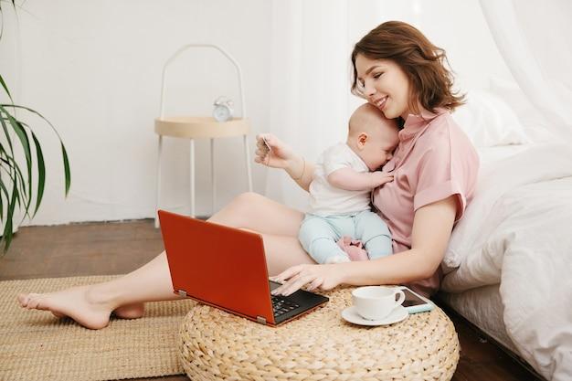 Portret van moeder en zoontje online winkelen met creditcard, met behulp van laptop. Premium Foto