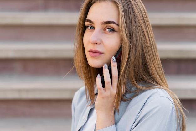Portret van mooi blondemeisje die op telefoon spreken Gratis Foto