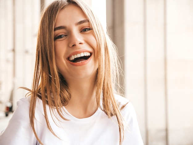 Portret van mooi glimlachend blond model gekleed in de zomer hipster kleren. Gratis Foto