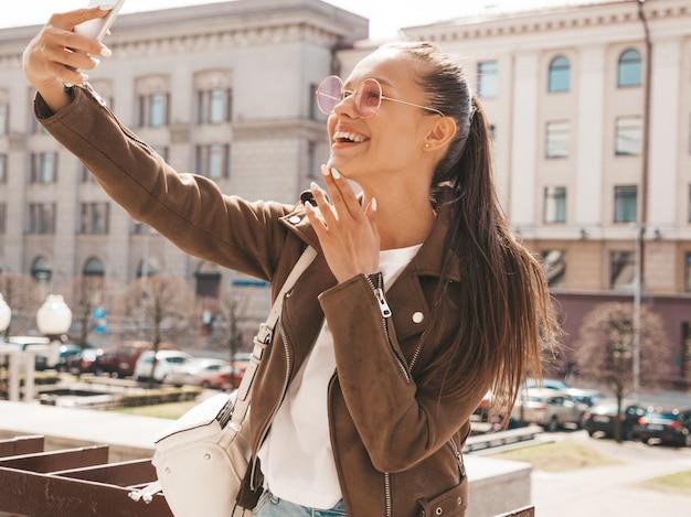 Portret van mooi glimlachend donkerbruin meisje in de zomer hipster jasje. model nemen selfie op smartphone. Gratis Foto