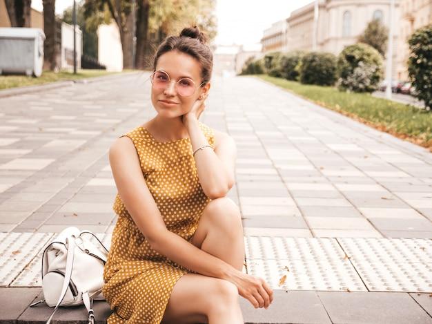 Portret van mooi glimlachend hipster model gekleed in de zomer gele kleding. trendy meisje poseren in de straat. grappige en positieve vrouw die pret heeft Gratis Foto