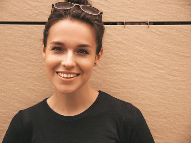 Portret van mooi glimlachend model gekleed in de zomerkleren. trendy meisje poseren in de straat. grappige en positieve vrouw die pret heeft Gratis Foto
