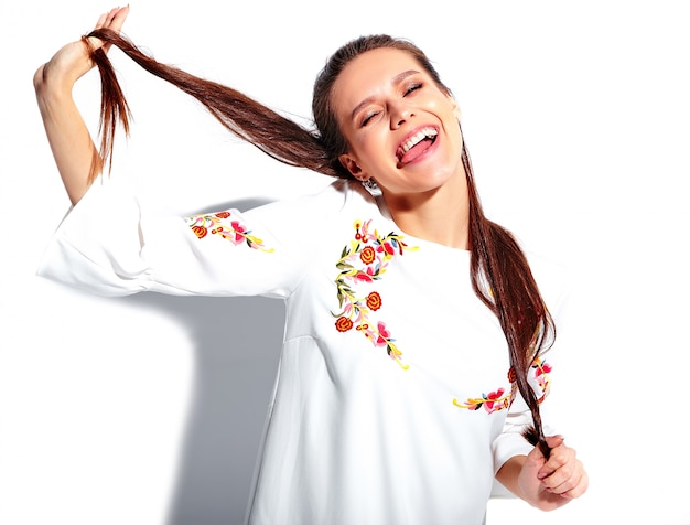 Portret van mooi kaukasisch het glimlachen donkerbruin vrouwenmodel in witte de zomer modieuze kleding dat op witte achtergrond wordt geïsoleerd. haar haar draaien Gratis Foto