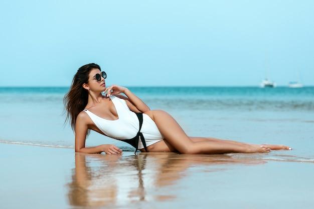 Portret van mooi kaukasisch sunbathed vrouwenmodel in een wit zwempak Premium Foto