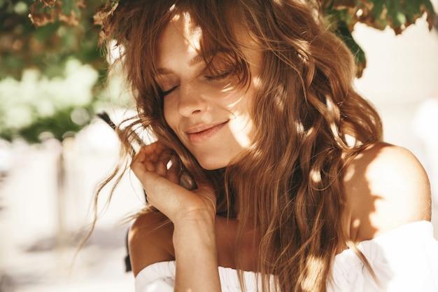 Portret van mooi leuk blond tienermodel zonder make-up in kleren van de de zomer hipster witte kleding die op de straatachtergrond stellen. sunglights op gezicht Gratis Foto
