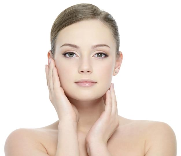Portret van mooi meisje dat haar mooi gezicht met gezonde huid streelt Gratis Foto