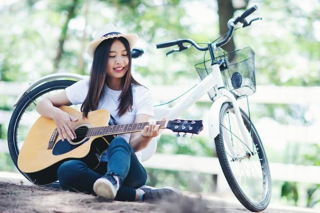 Portret van mooi meisje die de gitaar met fiets spelen bij aard Gratis Foto