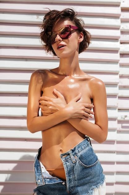 Portret van mooi meisje in denimborrels en zonnebril. mooi meisje permanent en haar borst bedekt met handen op het strand Premium Foto
