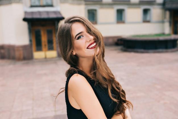 Portret van mooi meisje met lang krullend haar poseren op straat Gratis Foto