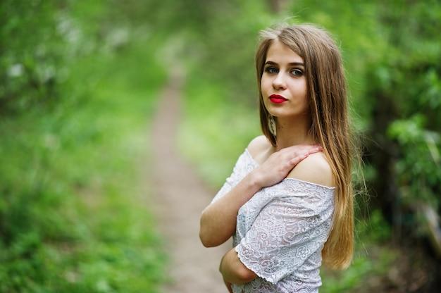 Portret van mooi meisje met rode lippen bij de tuin van de de lentebloesem, slijtage op rode kleding en witte blouse. Premium Foto