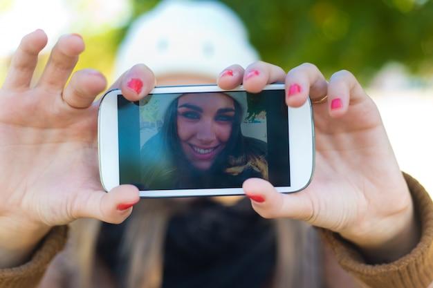 Portret van mooi meisje nemen een selfie met mobiele telefoon in Gratis Foto