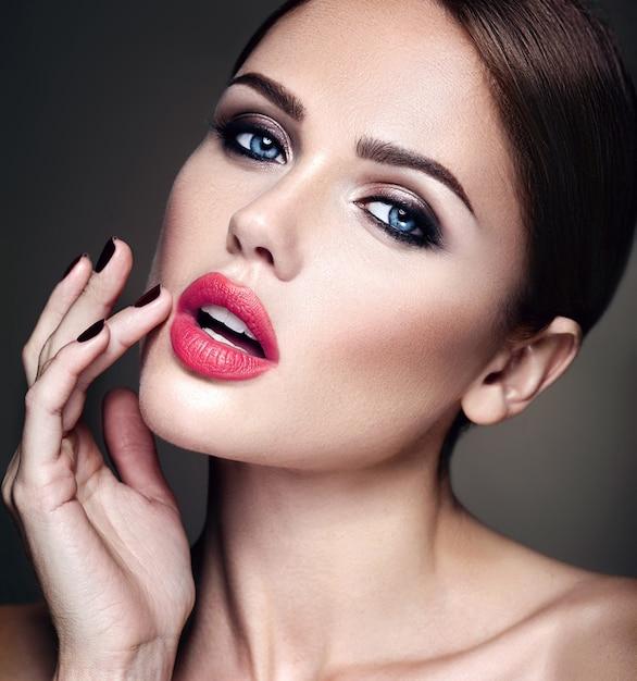 Portret van mooi meisjesmodel met avondmake-up en romantisch kapsel. haar rode lippen aanraken Gratis Foto