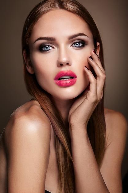 Portret van mooi meisjesmodel met avondmake-up en romantisch kapsel. rode lippen Gratis Foto