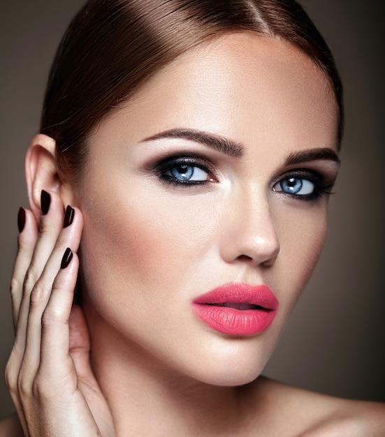 Portret van mooi meisjesmodel met avondmake-up en romantisch kapsel wat betreft haar huid. roze lippen Gratis Foto