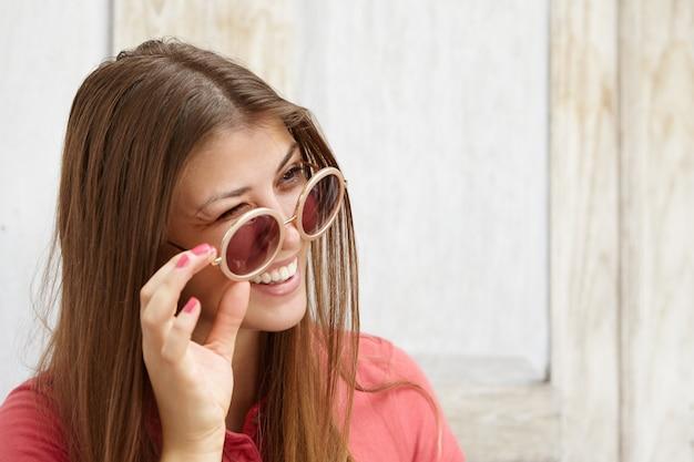 Portret van mooi speels meisje dat tinten draagt, knipoogt naar iemand met een flirtende glimlach, haar zonnebril opstijgt. Gratis Foto