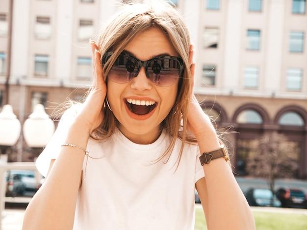 Portret van mooi verrast blond model gekleed in de zomer hipster kleren. het trendy meisje stellen op de straatachtergrond. grappige en geschokte vrouw Gratis Foto