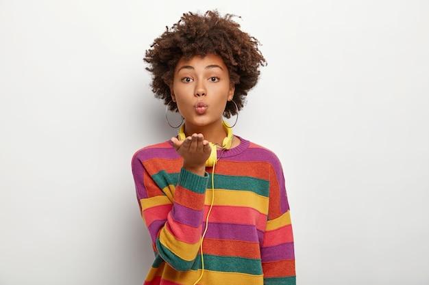 Portret van mooie aanhankelijk krullend tienermeisje houdt de handpalmen naar voren gestrekt, lippen afgerond, stuurt luchtkus, draagt casual kleurrijke trui, koptelefoon gebruikt voor het luisteren naar favoriete melodieën Gratis Foto