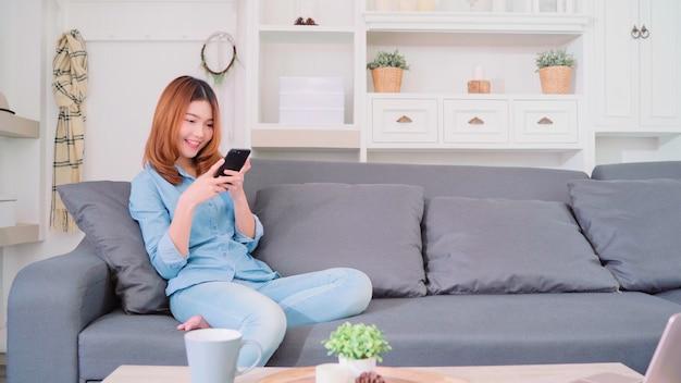 Portret van mooie aantrekkelijke jonge lachende aziatische vrouw met behulp van smartphone Gratis Foto