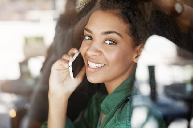 Portret van mooie afrikaanse vrouw achter glas glimlachen praten over de telefoon Gratis Foto