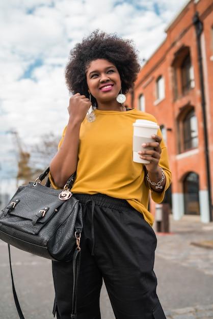 Portret van mooie afro amerikaanse latijns-vrouw lopen en houden een kopje koffie buiten in de straat. stedelijk concept. Gratis Foto