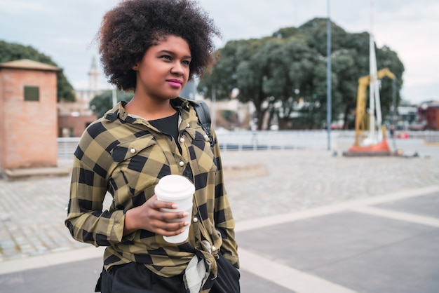 Portret van mooie afro amerikaanse latijns-vrouw met een kopje koffie buiten in de straat. stedelijk concept. Gratis Foto